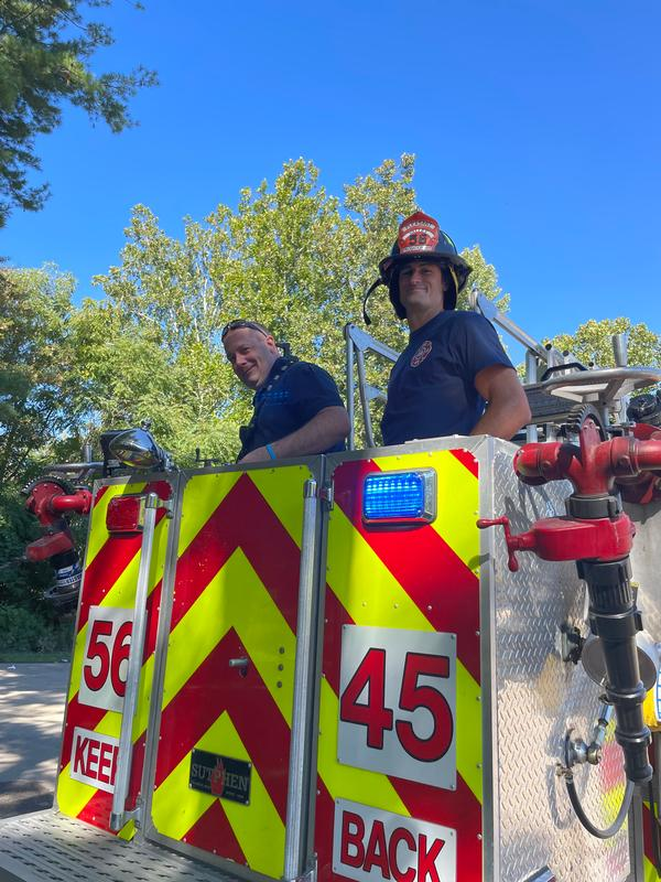 Firefighter Tom Murphy on left and new Probationary Firefighter Ethan Binford on right in the bucket of Ladder 56-45 on his first day at work.