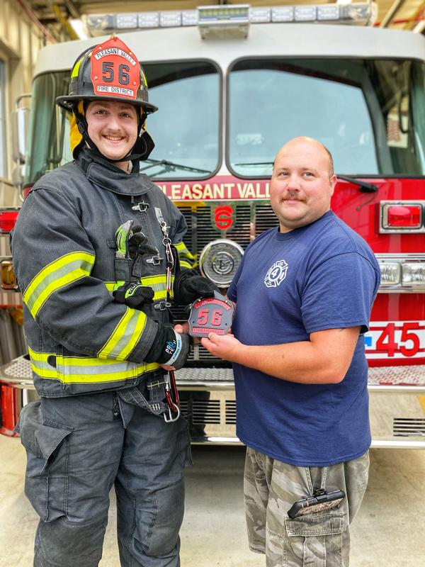 Deputy Chief Mark Luby presents Firefighter Jack Blanch with his new shield