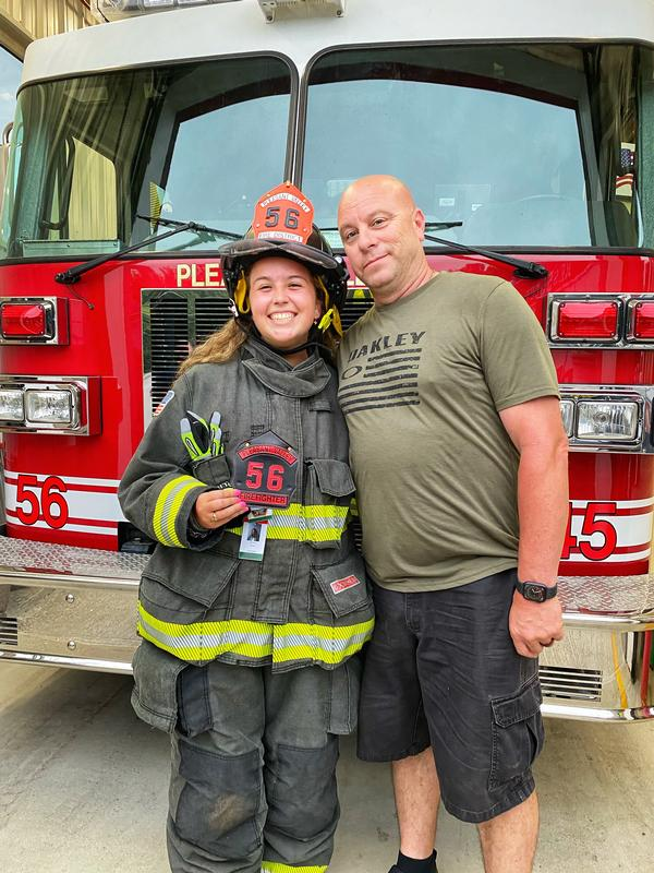Captain John Cronk presents Firefighter Martina Meyer with her new shield