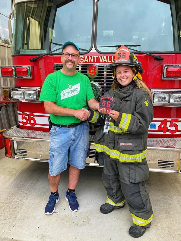 Lieutenant Jay Meyer congratulates his daughter Firefighter Martina Meyer after receiving her new shield
